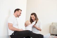 Parents et leur beau bébé s'asseyant sur la terre et jouer Photographie stock libre de droits