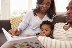 Parents et livre de lecture de fils sur Sofa At Home Together image libre de droits