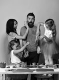 Parents et peinture d'enfants avec la gouache sur les filles, l'homme et la femme jaunes de fond avec les visages choqués et heur Photo stock