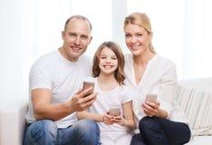 Parents et petite fille avec des smartphones à la maison Images libres de droits
