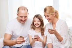 Parents et petite fille avec des smartphones à la maison Photo libre de droits