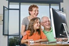 Parents et petite-fille avec l'ordinateur Photographie stock libre de droits