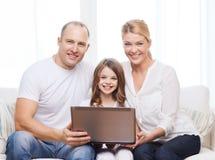 Parents et petite fille avec l'ordinateur portable à la maison Photo stock