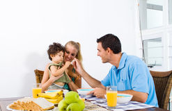 Parents feeding baby. Young parents feeding baby boy breakfast Stock Images