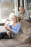 Parents feeding bottle to baby at home on couch Royalty Free Stock Photography