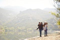 Parents ferroutant leurs enfants en bas âge par un lac de montagne photos libres de droits