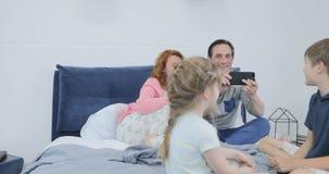 Parents filmant la vidéo des enfants jouant se reposant ensemble sur le lit dans la chambre à coucher, famille heureuse passant l banque de vidéos
