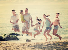 Parents with four children jumping. Happy parents with four children in different ages jumping on sea coast on sunny summer day Royalty Free Stock Images