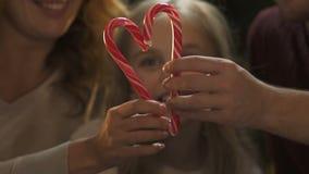 Parents gais formant le coeur de la canne de sucrerie, décorations de scintillement de Noël banque de vidéos