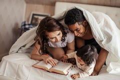 Parents gais lisant les queues féeriques à un bébé avant le sommeil de nuit images libres de droits