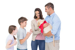 Parents gifting puppy to children against white background. Happy mother and father gifting puppy to children against white background Royalty Free Stock Photography