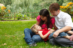 Parents with girl have rest in summer garden Royalty Free Stock Photo