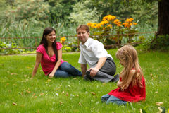 Parents with girl have rest in summer garden Royalty Free Stock Photography