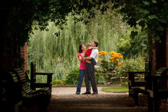 Parents and girl in summer garden in plant tunnel Royalty Free Stock Image