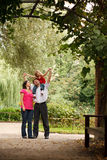 Parents and girl in summer garden in plant tunnel Stock Photos