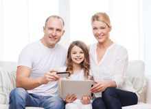 Parents and girl with tablet pc and credit card. Family, child, technology, money and home concept - smiling parents and little girl with tablet pc and credit Royalty Free Stock Images