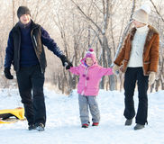 Parents and girl walking in a winter park Stock Photo