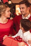 Parents giving child Christmas gift Stock Photography