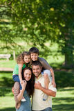 Parents giving children a piggyback Stock Image