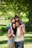 Parents giving children a piggyback Stock Photos