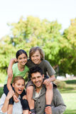 Parents giving children a piggyback Stock Photography