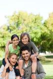 Parents giving children a piggyback Stock Photography