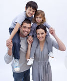 Parents giving children piggyback rides Stock Image