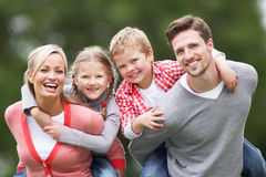 Parents Giving Children Piggybacks In Countryside Stock Images