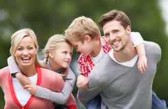 Parents Giving Children Piggybacks In Countryside Stock Photography