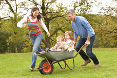 Parents Giving Children Ride In Wheelbarrow. Outside Royalty Free Stock Photos