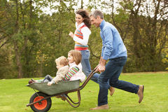Parents Giving Children Ride In Wheelbarrow Stock Photo