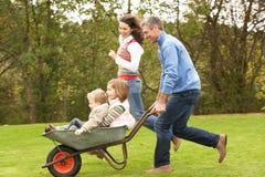 Parents Giving Children Ride In Wheelbarrow. Having Fun Stock Photo