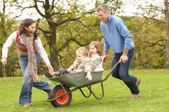 Parents Giving Children Ride In Wheelbarrow. In garden stock image
