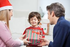 Parents Giving Christmas Present To Son. At home Stock Images