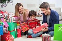 Parents Giving Christmas Present To Son. Smiling parents giving Christmas present to son at home Stock Photo