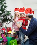 Parents Giving Gift To Boy By Christmas Tree. Happy parents giving gift to boy by Christmas tree at home Stock Photo