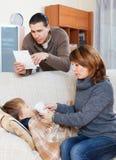 Parents giving liquid medicament to son. Parents giving liquid medicament to unwell son stock images
