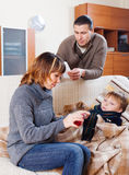 Parents giving liquid medicament to unwell son. Parents giving liquid medicament to unwell teenage son royalty free stock photos