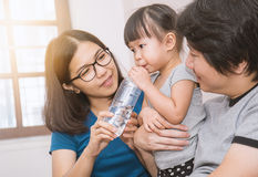 Parents giving little daughter a bottle with drink Royalty Free Stock Image