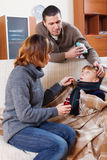 Parents giving  medicament to unwell  son Stock Photos