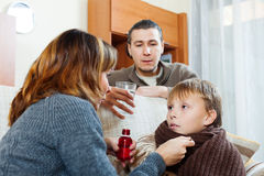 Parents giving medicinal sirup to  boy Royalty Free Stock Photography