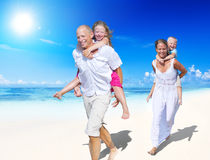 Parents Giving Piggy Backs to Children. Parents Giving Piggy Backs to Their Children by the Beach royalty free stock image