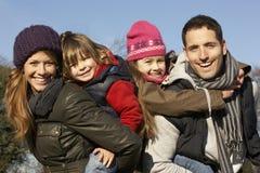 Parents giving piggybacks to children on winter walk Stock Photo