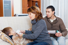 Parents giving pills to son. At home Royalty Free Stock Image