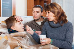 Parents giving pills to son. Loving parents giving pills to son at home stock photography