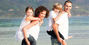 Parents giving two young children piggyback rides Royalty Free Stock Image