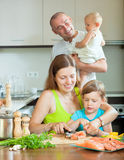 Parents with good kids cooking fish at home kitchen Stock Photos