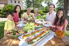 Parents Grandparents Children Family Eating. An attractive happy, smiling family of mother, father, grandparents, son and daughter eating healthy food at a Royalty Free Stock Photo