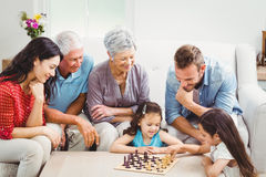Parents and grandparents looking at girls playing chess Royalty Free Stock Photography
