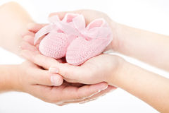 Parents hands holding baby booties. Mother's and father's hands holding pink newborn baby booties. Over white. Hand in hand Stock Photo